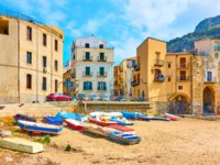 Италия. Сицилия. Панорама Чефалу. Boats on sandy beach and old colorful houses by the sea in the old town of Cefalu in Sicily, Italy. Фото Zoooom-Depositphotos