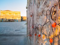 Close up view of a fishing net haung on the wall of a typical house in Marzamemi, Sicily, and one of the facade of the old tonnara at the sunrise. Фото siculodoc-Deposit