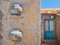 Colored ceramic jars set as ornaments into the external wall of a typical house in the fishing village Marzamemi, Southeast Sicily. Фото siculodoc - Depositphotos