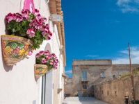 Decorated and flowered ceramic vases set into the wall of a house along the streets of Marzamemi, a small fishing village, southeastern Sicily. Фото siculodoc-Deposit
