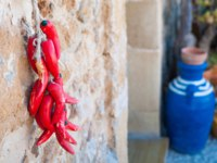 Small pile of fake red peppers hanging on the wall of a typical stone house in the fishing village Marzamemi, Sicily. Фото siculodoc - Depositphotos