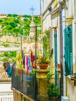 Италия. Сицилия. Модика. Houses with balconies overlooking a narrow street in Modica, Sicily, Italy. Фото Dudlajzov - Depositphotos
