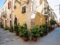 Италия. Сицилия. Сиракузы. View of one typical street in Ortigia, the old part of Syracuse, and some ornamental flowered vases. Фото siculodoc - Depositphotos
