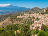 Италия. Сицилия. Таормина. Panoramic sight with Taormina and Etna volcano, from the Ancient Greek Theater. Province of Messina, Sicily, Italy. Фото e55evu-Deposit