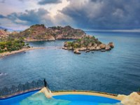 Италия. Сицилия. Таормина. Waterfront with view of town and island with famous Isola Bella beach. Taormina, Sicily, Italy. Фото Bareta - Depositphotos
