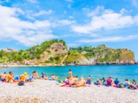 Италия. Сицилия. Таормина. People are enjoying summer on a beach near Isola Bella in Taormina, Sicily, Italy. Фото Dudlajzov - Depositphotos