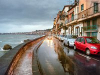 Италия. Сицилия. Таормина. Road along waterfront with cars and coastal houses at rainy twilight in Giardini Naxos near Taormina. Sicily. Фото Bareta-Deposit