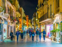 Италия. Сицилия. Таормина. People are strolling on a narrow street during night in Taormina, Sicily, Italy. Фото Dudlajzov - Depositphotos