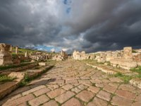 Клуб путешествий Павла Аксенова. Иордания. Джераш. A Roman road in the ancient city of Gerasa after a storm with dark grey clouds. Фото Celcinar - Depositphotos