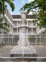 Маврикий. Порт-Луи. Port Louis, Mauritius. Statue of Queen Victoria, Government House, French Colonial building still used by the current government. Фото vale_t - Depositphotos