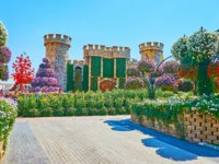 ОАЭ. Дубай. Сад чудес. The scenic small castle replica with lush shrubs, sunflowers and petunia in pots around it, Miracle Garden in Dubai. Фото efesenko - Depositphotos