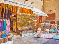 The stall of Bur Dubai Grand Souq with wide range of colorful pottery, pillows with fine embroidered patterns and Arabic attire. Фото efesenko - Depositphotos