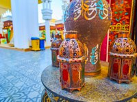 ОАЭ. Дубай. Всемирная деревня. Traditional Arabian lights on the carved table in Morocco pavilion of Global Village Dubai in Dubai. Фото efesenko - Depositphotos