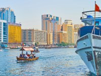 The abra boat floats along Dubai Creek with a view on moored ship and modern quarters of Deira in Dubai. Фото efesenko - Depositphotos