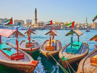 The old wooden abra boats of Dubai Creek in Deira district; Grand Mosque and Bur Dubai houses in Dubai.  Фото efesenko - Deposit