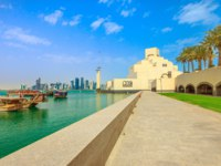 Катар. Доха. Музей исламского искусства. Doha seafront with palm trees and West Bay skyline along Corniche in Qatar with Dhow Harbour. Фото bennymarty - Deposit