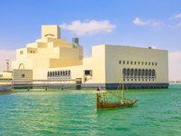 Катар. Доха. Музей исламского искусства. Museum of Islamic Art in Doha Bay with Dhow boat, icon of urban cityscape. Qatari capital. Фото bennymarty - Depositphotos