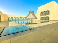 Катар. Доха. Музей исламского искусстваCourtyard of Museum of Islamic Art with fountains and arched Doha West Bay reflecting. Doha. Фото bennymarty - Depositp