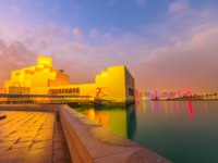 Катар. Доха. Музей исламского искусства. Doha seafront and West Bay skyline reflecting in Doha Bay along Corniche in Qatari capital. Фото bennymarty - Depositphotos