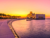Катар. Доха. Музей исламского искусства. The walkway with palm trees along Doha Bay. Museum and dhow. Scenic urban cityscape. Фото bennymarty - Depositphotos