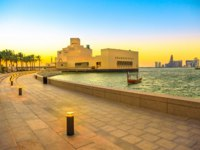 Катар. Доха. Музей исламского искусства. Seafront walkway with palm trees along Doha Bay with museum, Doha West Bay. Qatar. Фото bennymarty - Depositphotos