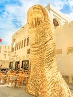 Golden giant thumb sculpture at Souq the old traditional market. The souq is considered one of best location for tourists in Doha. Qatar. Фото bennymarty-Deposit