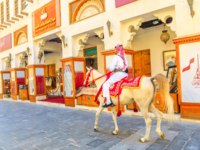 Катар. Доха. One police on horse in clothes at old Souq Waqif riding white Arabian Horses on main street. Popular tourist attraction in Doha. Фото bennymarty-Deposit