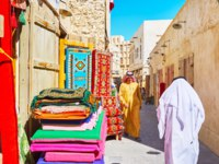Доха. The carpet store in narrow street of Souq Waqif, locals walk along the road in attire-keffiyeh (headscarf) and dishdasha or thobe (robe). Фото efesenko-Deposit