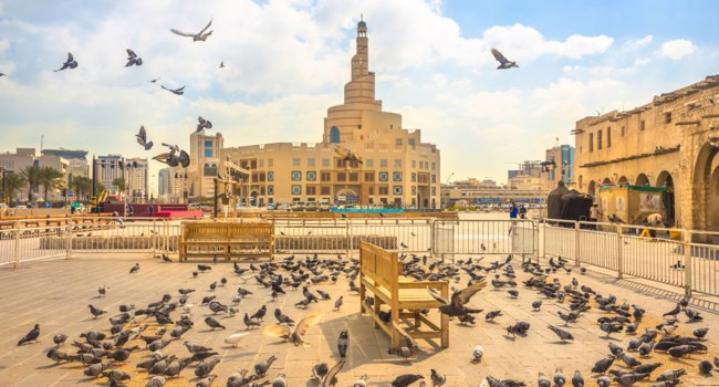 Катар. Доха. Рынок Сук-Вакиф. Many pigeons flying in Souq Waqif square. Cultural Center with Spiral Mosque and Minaret. Doha. Qatar. Фото bennymarty-Deposit