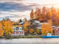 Золотое кольцо России. Плес. Colorful houses on the shore among red autumn trees in Ples. View from the water of the Volga. Фото yulenochekk - Depositphotos