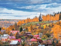 Плес. Wooden Church of the Resurrection on Mount Levitan in the city of Plyos among red autumn trees and multi-colored houses. Фото yulenochekk - Depositphotos