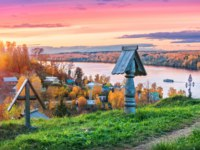 Золотое кольцо России. Плес. Wooden crosses on Mount Levitan in Plyos and a view of the Volga against a pink sunset autumn sky. Фото yulenochekk - Depositphotos