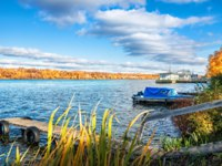Золотое кольцо России. Плес. View of the Volga in the city of Plyos, wooden walkways and a pier with boats on an autumn day. Фото yulenochekk - Depositphotos