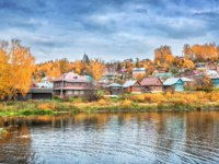 Золотое кольцо России. Плес. Wooden colorful houses of Plyos on the banks of the river Shokhonki among red autumn trees. Фото yulenochekk - Depositphotos