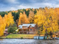 Золотое кольцо России. Плес. Wooden log house on the shore in the city of Plyos among red autumn trees. Фото yulenochekk - Depositphotos