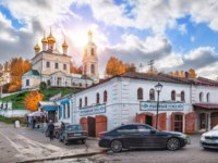 Золотое кольцо России. Плес. Shop Fish Corner and the Resurrection Church in the city of Plyos in the autumn sunny day. Фото yulenochekk - Depositphotos
