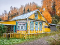 Золотое кольцо России. Плес. Yellow wooden house in Plyos with white lace windows among red autumn trees. Фото yulenochekk - Depositphotos