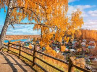 Золотое кольцо России. Плес. Yellow birch on Cathedral Mountain in Plyos and a view of colorful houses in autumn sunny day. Фото yulenochekk - Depositphotos