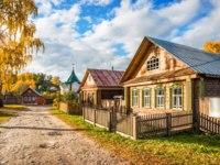 Золотое кольцо России. Плес. Wooden house of artists in Russian style in autumn Plyos on a sunny afternoon and Nikolskaya chapel. Фото yulenochekk - Depositphotos