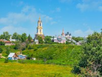 Суздаль. The tall bell tower of Smolenskaya Church (Our Lady of Smolensk) and Simeonovskaya church behind the green hill in Suzdal, Russia. Фото efesenko-Deposit