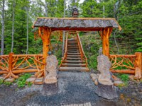 Ornate wooden gate with cariving bird statues and fense at the entrance to the observation deck of waterfall Tokhmajoki (Ruskeala). Karelia. Фото Igor-SPb-Deposit