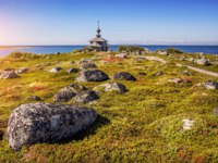 Клуб Павла Аксенова. Россия. Соловецкие острова. Church of St. Andrew on the island Zayatsky and boulders in the grass. Фото yulenochekk-Depositphotos