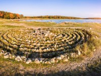 Россия. Соловецкие острова. Pattern made of stones in the form of a labyrinth on the shores of the White Sea at sunset. Фото yulenochekk-Depositphotos