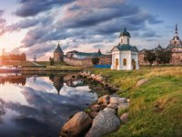 Россия. Соловецкие острова. Picture wall of the Solovetsky monastery and chapel with the reflection in the bay under the rain clouds. Фото yulenochekk-Depositphotos