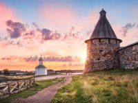 Россия. Соловецкие острова. The sun peeks out from behind the tower of the Solovetsky monastery and chapel on the shore. Фото yulenochekk-Depositphotos