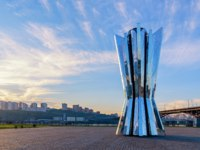 Россия. Красноярск. VTorch-a geometric figure with a mirror surface, an abstraction, a monument under the setting sun. Krasnoyarsk. Фото Razgulyaev - Depositphotos