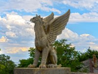 Россия. Крым. Город-герой Керчь. Statue of a griffin shot against cloudy sky. Фото Yurriy - Depositphotos