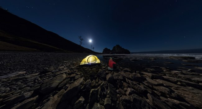 Россия. Озеро Байкал. Panorama of  man at  tent on  stone beach on shore of Lake Baikal at night. Фото kirzaa@mail.ru - Depositphotos