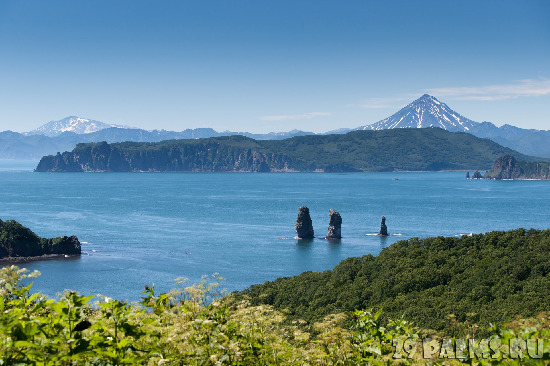 Россия. Камчатка. The cliff Three Brothers and the hill Vilyuchinsky volcano in the background. Kamchatka Peninsula, RussiaФото Valeryet - Depositph