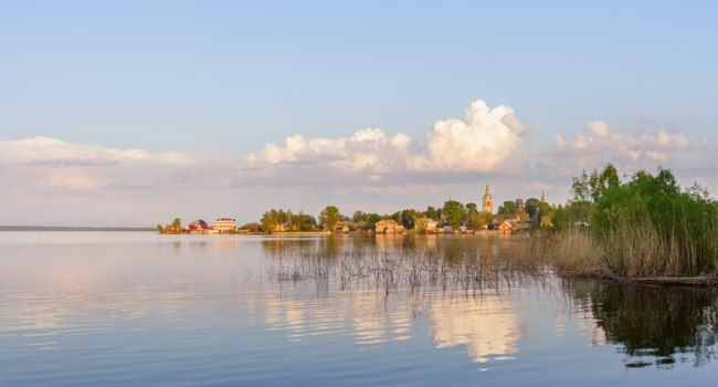 Россия. Озеро Селигер. Rural landscape with a lake and a town of Ostashkov on the beach. Фото TischenkoPhoto - Depositphotos